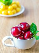 stock photo of cherry  - In a cup red sweet cherries with mint leaves lie on a background there is a saucer with a yellow sweet cherry - JPG