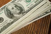 foto of bundle money  - Bundle of money on brown wooden background - JPG