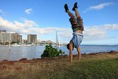 stock photo of waikiki  - Man wearing shorts shirt and shoes Handstanding along shore of Magic Island with Ala Wai Boat Harbor Waikiki Diamond Head in the distance looking into the pacific ocean on Oahu Hawaii on a beautiful day - JPG