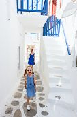 stock photo of greek-island  - Family of mother and daughter at street of typical greek traditional village with white walls and colorful doors - JPG