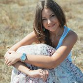 pic of jeans skirt  - Portrait of beautiful young woman which sits on grass on natural background - JPG