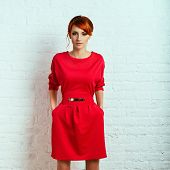 picture of young woman posing the camera  - Beautiful young fashionable woman posing in red dress smiling looking at camera - JPG