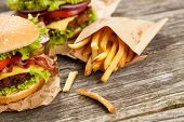 stock photo of hamburger-steak  - Delicious hamburger and french fries on wooden background - JPG
