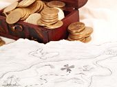 foto of treasure chest  - Treasure chest full of golden coins next to a treasure map - JPG