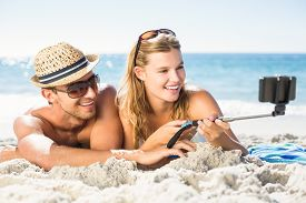 image of selfie  - Happy couple taking selfie with selfie stick at the beach - JPG