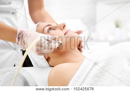poster of Beautiful neckline, microdermabrasion. Relaxed woman during a microdermabrasion treatment in beauty salon