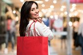 Smiling woman holding a shopping bag in a shopping mall poster