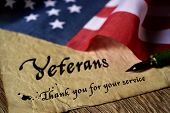 the text veterans than you for your service written in a piece of paper with a nib pen and a flag of poster