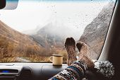 Woman legs in warm socks on car dashboard. Drinking warm tee on the way. Fall trip. Rain drops on wi poster