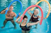 Portrait of smiling people doing aqua fitness together in a swimming pool. Group of senior woman and poster