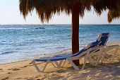 Lounge chairs on a tropical beach under a palapa.