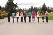 Ten beautiful girls, walking together hand in hand.