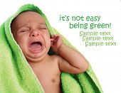Crying newborn baby wrapped in a green towel.