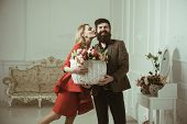 Birthday Concept. Sensual Woman Kiss Bearded Man With Birthday Flowers. Bearded Man Give Basket With poster