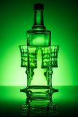 Bottle Of Absinthe With Glasses On Mirror Surface And Dark Green Background poster