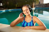 Relaxed Smiling Woman Listening To Music In Headphones Bathing In Swimming Pool. Blonde Girl Enjoys  poster