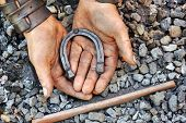 picture of blacksmith shop  - Detail of dirty hands holding horseshoe  - JPG