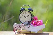 Black Alarm Clock Stacked On Old Dictionary With Pink Flower And Glasses poster