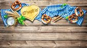 Rustic background for Oktoberfest with white and blue fabric, hop, silverware, beer glass and pretze poster
