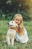 Little Cute Blond Girl Playing With Her Puppy Golden Retriever In Summer In The Park. poster
