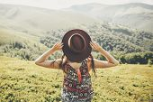 Travel And Wanderlust Concept. Traveler Hipster Girl Holding Hat, Looking At Sunny Mountains. Summer poster
