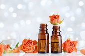 Rose Essential Oil Bottles On White Table With Bokeh Effect. Spa, Aromatherapy, Wellness, Beauty Bac poster