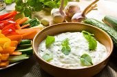 picture of raita  - A bowl of tzatziki dip and fresh cut vegetable sticks next to it - JPG