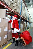stock photo of santa-claus  - Santa claus looking for presents  in storehouse - JPG