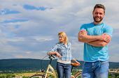 Man Bearded Macho Posing Confidently In Front Of Shy Girl With Bike. Cycling Instructor Concept. Nev poster