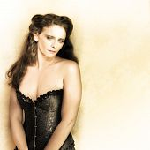 foto of forlorn  - Vintage pinup portrait of a beautiful woman wearing black corset fashion with a demure forlorn look - JPG