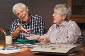 Senior Couple Choosing Photos For Album