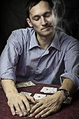 stock photo of sharpie  - young man with cigar playing poker - JPG