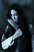 picture of gory  - Portrait of a gory and scary zombie woman on black background licking bloody knife - JPG