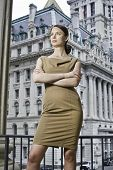 foto of cross-dressing  - Dressing formally a professional woman is crossing arms and seriously standing in a business district - JPG