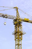 Yellow Hoisting Crane And Blue Sky