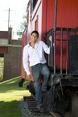 image of caboose  - Teenage boy standing on the steps of a red caboose - JPG