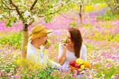 Happy couple on picnic in beautiful blooming garden, eating healthy organic food, romantic date, sum