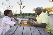 Senior couple playing game of backgammon