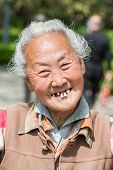 SHANGHAI, CHINA - APR 7, 2013: old chinese woman friendly toothless toothy smiling outddors portrait