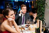 Man talking on a cell phone while on a date with his girlfriend or wife