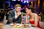 stock photo of feeding  - Affectionate couple in restaurant - JPG
