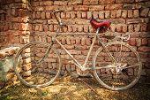 Постер, плакат: Пыльный старый велосипед в кирпичной стене