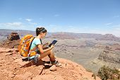 Tablet computer woman hiking in Grand Canyon using travel app or map during her hike. Multiethnic hi