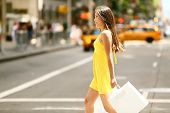 Shopping woman walking outside in New York City holding shopping bags. Shopper smiling happy crossin