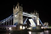 stock photo of hamlet  - Tower Bridge at night with its drawbridge open on the River Thames in Tower Hamlets - JPG