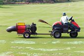 stock photo of leaf-blower  - Fairway turbine blower working golf driving range - JPG
