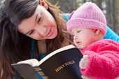 stock photo of bible verses  - Baby girl and mom reading KJV Bible  - JPG