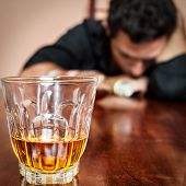 Portrait of a drunk  man addicted to alcohol sleeping with his head on the table  (Focused on the dr
