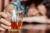 Drunk woman holding an alcoholic drink and sleeping with her head on the table (Focused on the drink