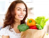 Happy Young Woman with vegetables in shopping bag . Beauty Girl in the kitchen Cooking healthy Food. Diet Concept